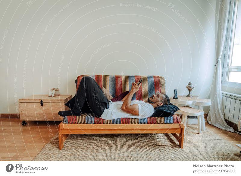 Ein spanischer Mann lag entspannt auf einem bunten Reisebus. Er benutzt ein Smartphone. Mobile Telefon im Innenbereich heimwärts Handy Person Menschen Morgen 1