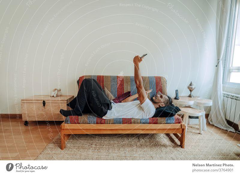 Ein spanischer Mann liegt entspannt auf einer bunten Couch. Er schreibt eine SMS und benutzt ein Smartphone. Mobile Telefon im Innenbereich heimwärts Handy
