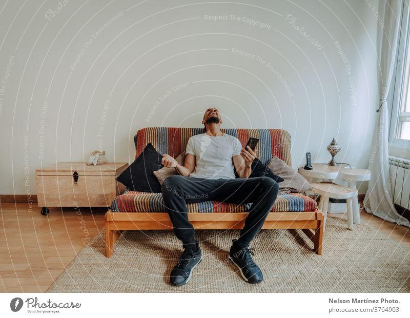 Ein spanischer Mann sitzt auf der Couch. Er lacht mit seinem Smartphone in der Hand. 1 Freiheit Erwachsener Blick Freizeitkleidung Lachen Lifestyle Feiertag