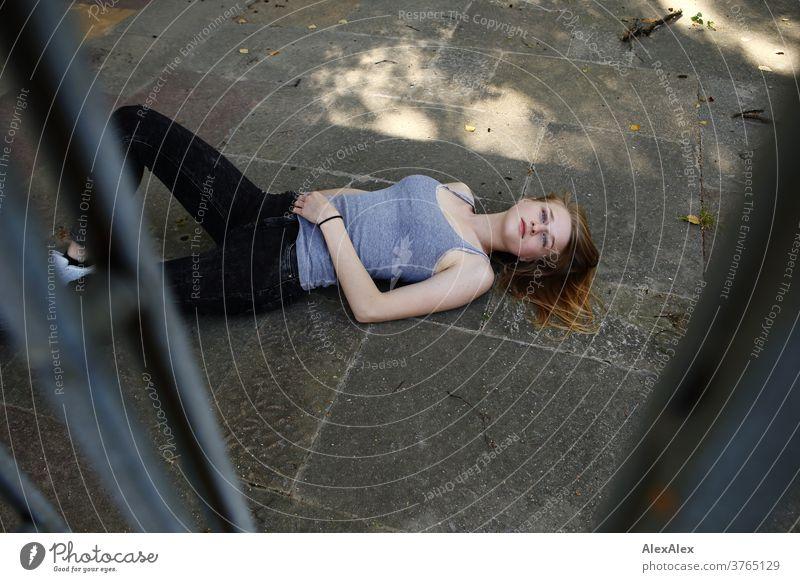 Portrait einer jungen Frau, die hinter einem Schiebegitter auf dem Boden liegt junge Frau schlank schön athletisch blond 18-25 Jahre rotblond Haare schauen