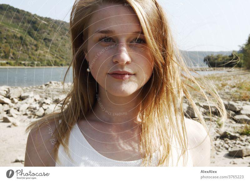Nahes Gegenlicht- Portrait einer jungen, sommersprossigen Frau mit vom Winde verwehten Haaren am Rheinufer junge Frau schlank schön athletisch blond 18-25 Jahre