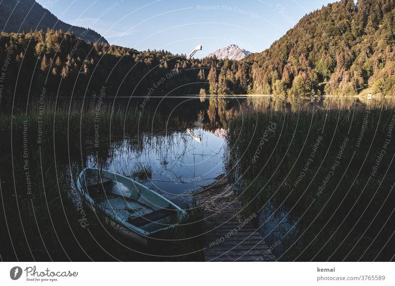 Boot und Steg an einem See Wasser Idylle Reflexion & Spiegelung Natur Berg Allgäu skisprungschanze Wald Bäume Ufer Schilf Ruderboot