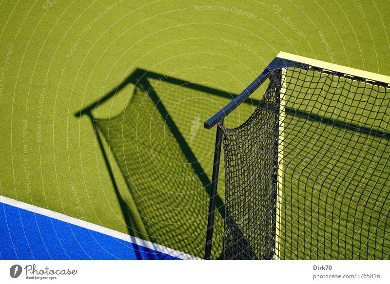 Hockeyplatz, menschenleer Sport Tor Hockeytor Licht Lichtspiel Schattenspiel selektiver fokus Netzwerk Tornetz Linie Grundlinie Spielen Freizeit & Hobby