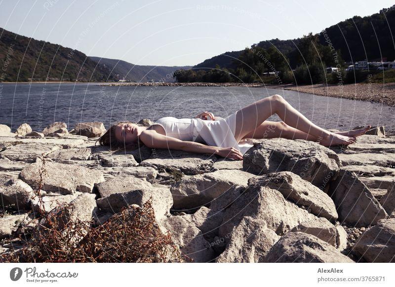 Gegenlicht- Portrait einer jungen, barfüßigen Frau am Rheinufer, die auf einem Damm liegt junge Frau schlank schön athletisch blond 18-25 Jahre rotblond Haare