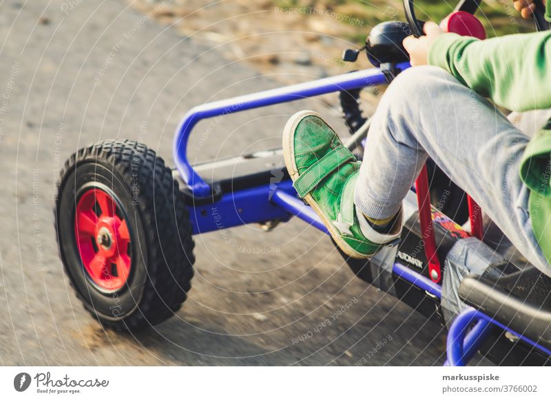 Junge mit Vintage Retro Kettcar spielen Spielplatz Fahrzeug Vierrad Antrieb Fuß Bein Kraft Lenkrad Kindheit Abenteuer Spielplatzgeräte Spaß haben glücklich