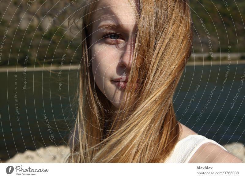 Nahes Portrait einer jungen Frau mit vom Winde verwehten Haaren in weißem Kleid vor Rheinufer junge Frau schlank schön athletisch blond 18-25 Jahre rotblond