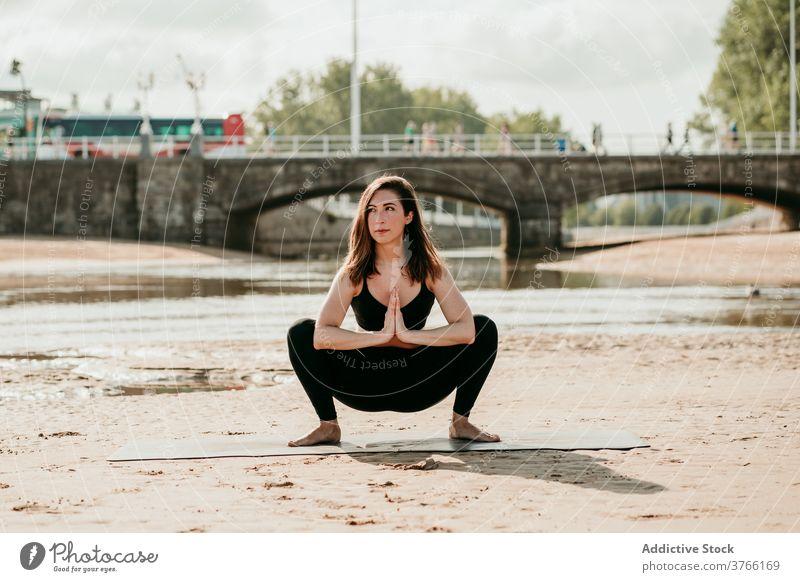 Schlanke Frau in Garland-Pose beim Yoga am Strand Girlandenpose malasaña üben Gleichgewicht Sommer Asana Ufer Unterlage ruhig Fluss Gesundheit schlank Harmonie