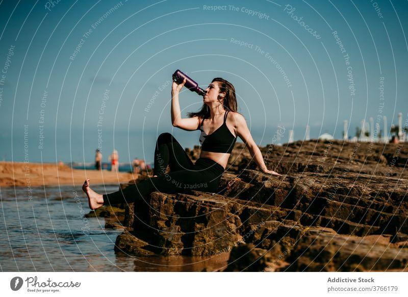 Ruhige Frau sitzt und trinkt Wasser nach Yoga trinken Ufer padmasana Zen Stressabbau Stein Sportbekleidung Wellness ruhig friedlich Harmonie üben