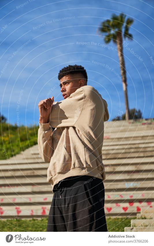 Junger Mann in Sportkleidung trainiert auf einer Treppe Übung Training Aufwärmen Schritt selbstbewusst jung ethnisch Sportler männlich Bestimmen Sie Athlet