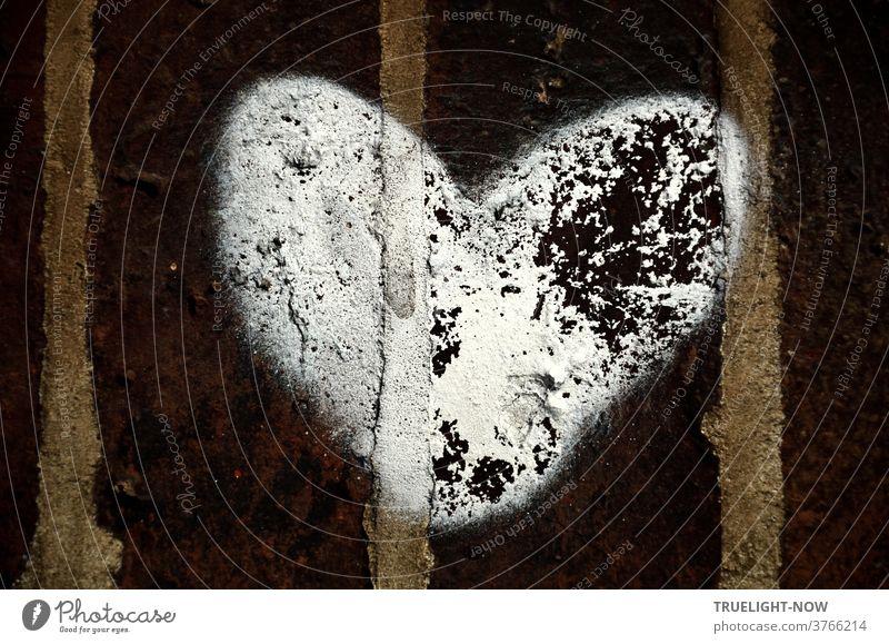 Dunkelbraune Ziegelsteine, die mit grauen Mörtel Fugen verbunden sind, hat jemand mit einem großen weissen Herz bemalt, dessen Farbe stellenweise schon abgeplatzt ist