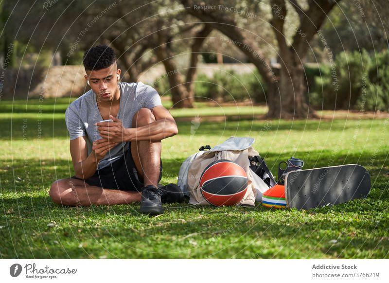 Schwarzer sportlicher Mann sitzt auf Rasen und benutzt Smartphone Sportler Basketball sich[Akk] entspannen Training Talkrunde Athlet Sommer männlich ethnisch