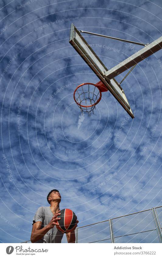 Männlicher Basketballspieler, der den Ball in den Korb schießt punkten Reifen Mann Spiel Spieler spielen springen Gericht männlich schwarz Afroamerikaner