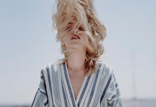 Bildnis einer kaukasischen blonden Frau.  Sie schüttelt den Kopf und die Haare bedecken ihr Gesicht. Kaukasier schütteln Behaarung Mode lebenslang konzeptionell