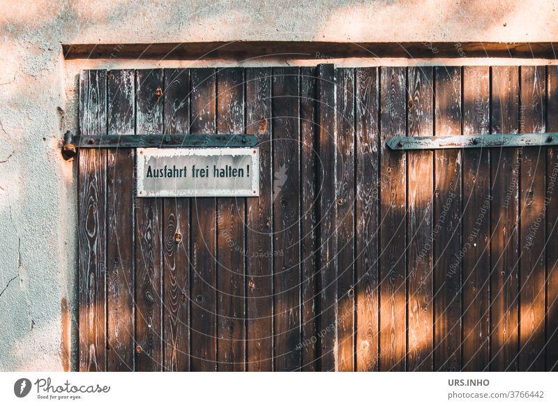 vor dem alten Garagentor soll nicht geparkt werden Tor vintage Tür Doppeltür Schild Einfahrt Tag Ausfahrt freihalten parken verboten Warnschild Hinweisschild