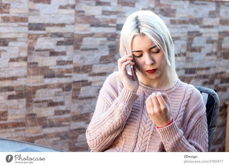 Glückliche blonde junge Frau sitzt im Freien und telefoniert mit ihrem Handy Mobile Person Erwachsener Telefon Mitteilung Technik & Technologie Lifestyle schön