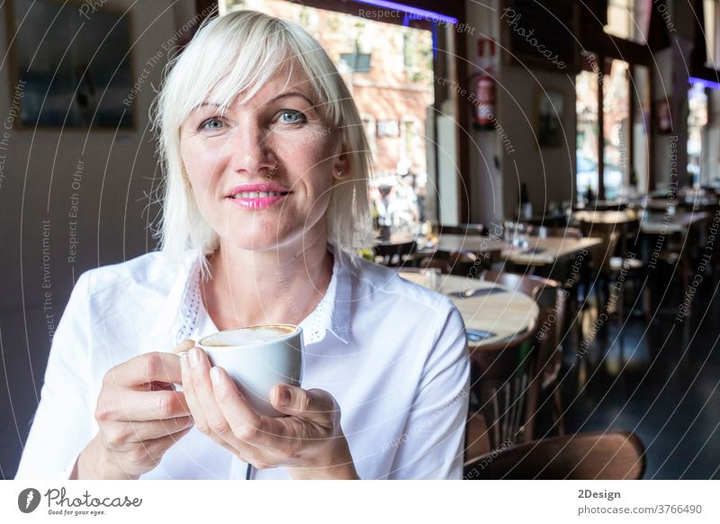 Junge blonde Frau trinkt Kaffee im Café Person Sitzen Tasse Lifestyle Tisch Lächeln Business Mädchen jung im Innenbereich Glück Erwachsener schön trinken