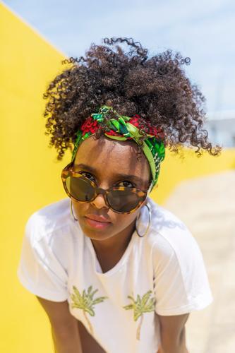 Attraktive junge afroamerikanische Frau mit Sonnenbrille und Stirnband Afro-Look Behaarung 1 schwarz modisch Frisur lockig Mode Dame Person schön Mädchen