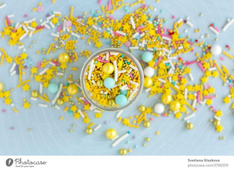 Gelbe Zuckerstreusel körnig auf blauem Hintergrund, Nahaufnahme flachgelegt farbenfroh Bonbon Farbe süß Lebensmittel Dessert Geburtstag Feiertag rosa Kuchen