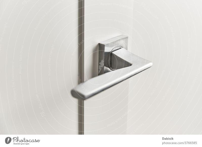 Silberner Türgriff an einer weißen Tür.  Möbelzubehör, Innenelement Handgriff modern Stahl Haus Schloss offen heimwärts Metall metallisch Innenbereich