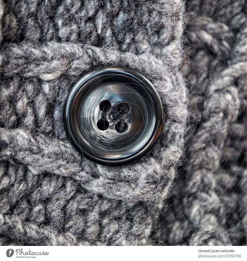 schwarzer Knopf in grauer Wolle, grauer Hintergrund Faser Gewebe Stoff texturiert abstrakt Muster Material Industrie Textil Design handgefertigt Detailaufnahme
