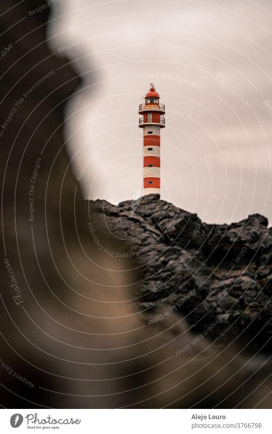 Rot-weißer Leuchtturm, gesehen hinter Vulkangestein an einem grauen Tag. Leuchtfeuer Gebäude Kanarienvogel Küste Küstenlinie Europa Gran Canaria Haus Insel