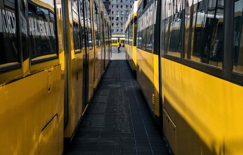 Straßenbahnen von allen Seiten und eine passend gekleidete Frau gelb Berlin Tram Verkehr urban Person Passant Perspektive Tunnelblick Fenster Fluchtpunkt