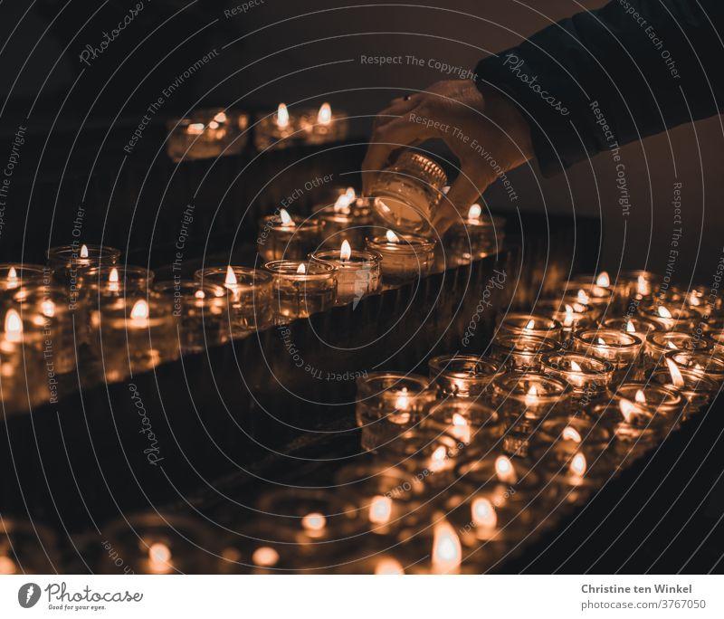 Kerzenaltar in einer Kirche. Weibliche Hand zündet eine Kerze an. Lichtermeer. Religion & Glaube Liebe Hoffnung Trauer Gedenken Gebet Christentum Kerzenschein