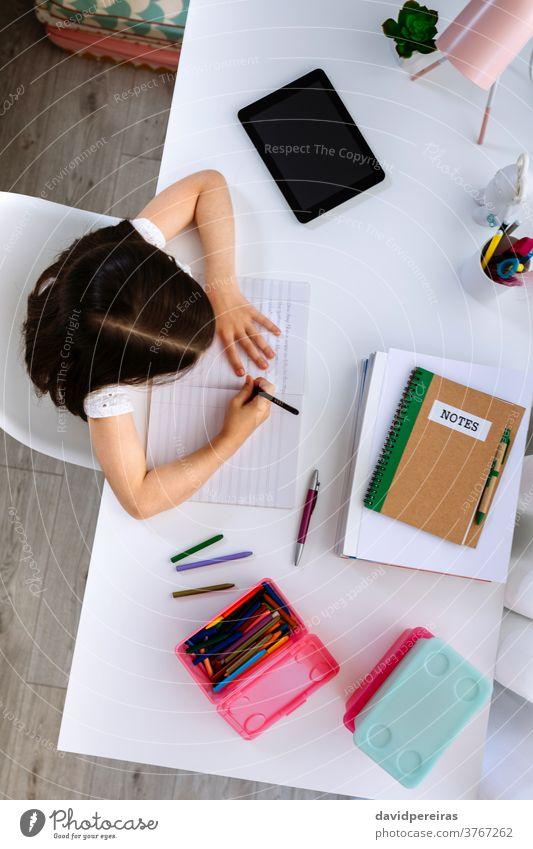 Mädchen macht Hausaufgaben am Schreibtisch sitzend Draufsicht unkenntlich schreibend Schule heimwärts Bildung konzentriert Kind Overhead Schule zu Hause Buch