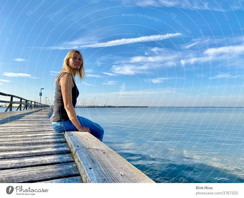 Blonde Frau sitzt auf einer Seebrücke an der Ostseeküste 45-60 Jahre schön blond Porträt anschauend Blick Mensch Erwachsene feminin Blick in die Kamera