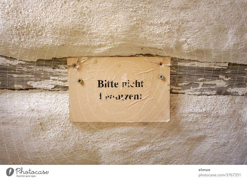 """""""Bitte nicht benutzen"""" steht unleserlich in schwarzer Druckschrift auf einem vergilbten Zettel, der an einem Holzbalken einer alten Wand befestigt ist. Verbot"""