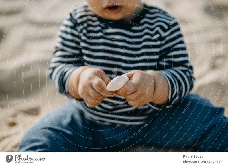 Kleinkind spielt mit Muschel am Sandstrand Salzwassermuschel Strand Badeurlaub Stranddüne reisen Kaukasier Neugier Ferien & Urlaub & Reisen Muschelschale