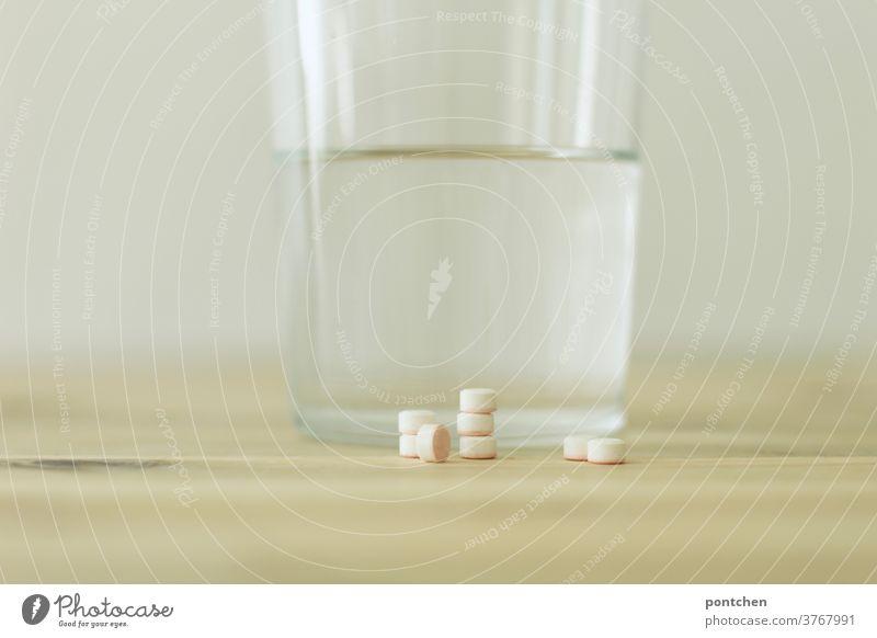 Mehrere Tabletten aufgestapelt liegen vor einem Trinkglas gefüllt mit Wasser auf einem Tisch. Krankheit, Medikamente. Tablettensucht. medizin wasserglas