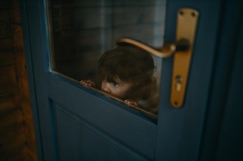 Kind schaut durch die Tür Kindheit Blick Glas Kaukasier Weihnachten & Advent Einsperrung Quarantäne zu Hause heimwärts zu Hause bleiben Farbfoto covid-19