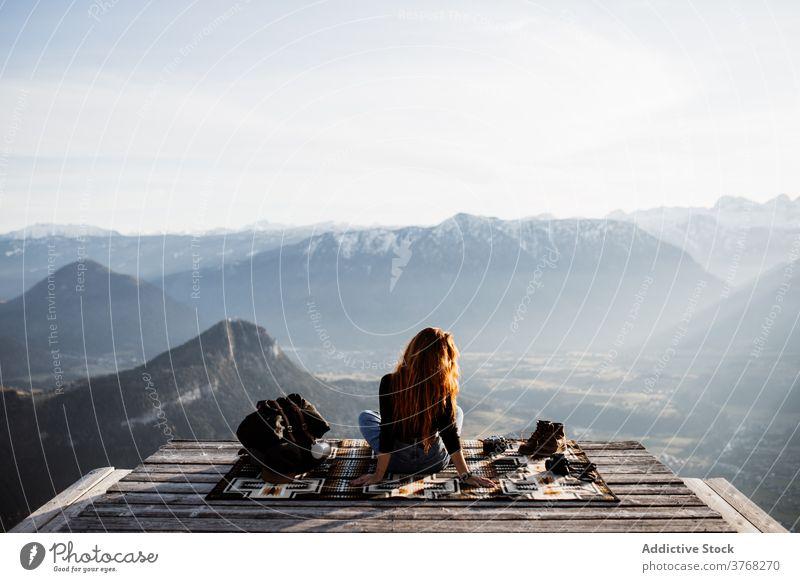 Reisende Frau auf Holzterrasse im Hochland Aussichtspunkt Berge u. Gebirge Morgen Reisender Nebel Sonnenstrahlen ruhig genießen Deutschland Österreich Tourist
