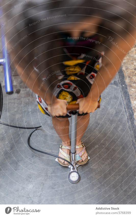 Frau füllt Fahrradreifen in der Werkstatt auf Reparatur Pumpe aufblasen Reifen Mechaniker fixieren Flugzeugwartung Beruf Dienst ethnisch professionell Arbeit