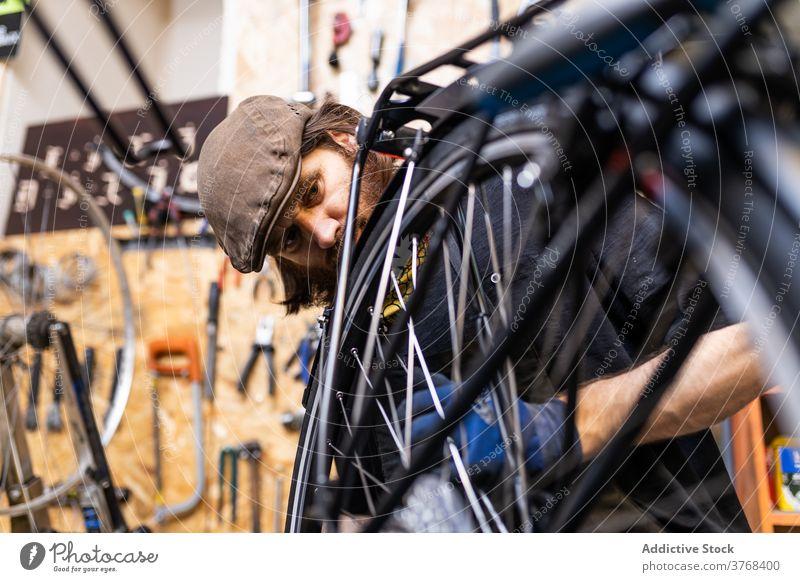 Reparateur repariert Fahrradrad in der Werkstatt Reparatur Mann Mechaniker Rad Speiche fixieren Flugzeugwartung Beruf Dienst männlich Vollbart reif