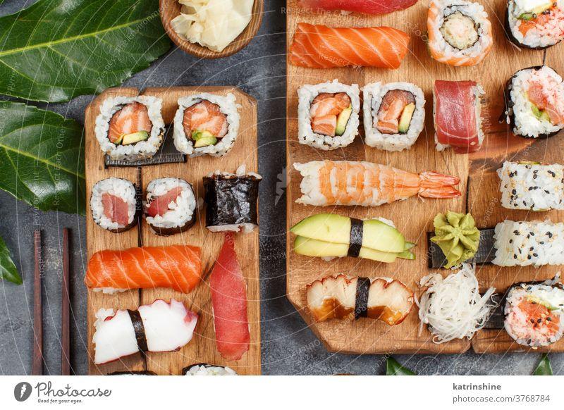 Sushi Set Nigiri und Sushi-Rollen auf rechteckigen Holzplatten verzehrfertig Essen Sashimi Brötchen maki Sushi-Bar Esszimmer Japanische Kultur Meeresfrüchte