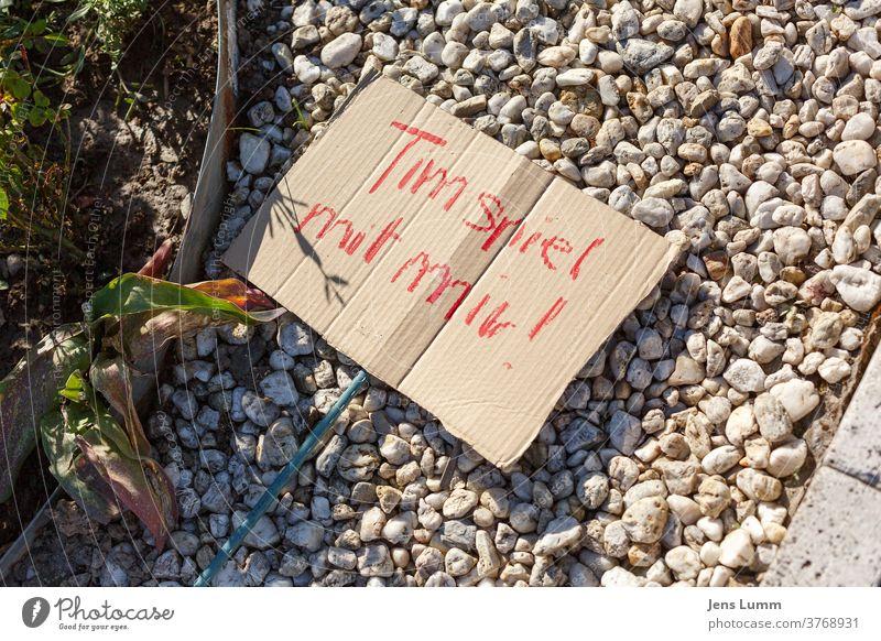 """Ein Schild mit den Worten """"Tim spiel mit mir!"""" Pappe rot Kiesbett Pflanze Garten Sommer spielende Kinder Spielen verboten corona Einsamkeit social distancing"""