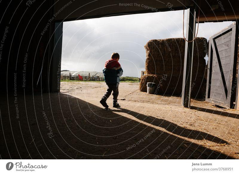 Junge verlässt Scheune auf Bauernhof Kind Schatten Heu Heuballen kalt Sommerurlaub bewölkter himmel Niederlande Sonnenlicht in Gedanken versunken grübeln