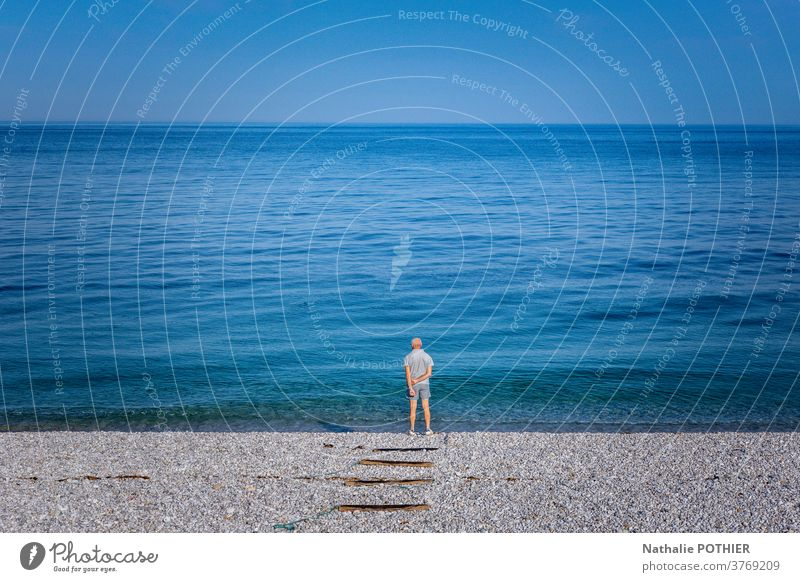 Einsamer Mann am Strand mit Blick auf den Horizont Landschaft MEER Meer allein zuschauend Blauer Himmel Blaues Meer Stehen Natur Ansicht im Freien Hintergrund