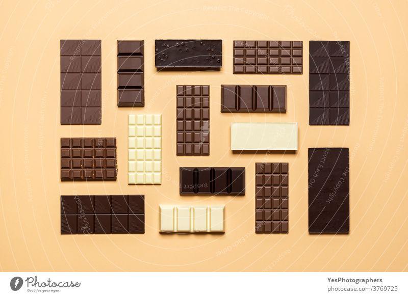 Schokoladentafel-Sortiment isoliert auf gelbem Hintergrund. Kreatives Schokoladen-Layout sortiert backen beige bitter Weihnachten Sammlung Konditorei