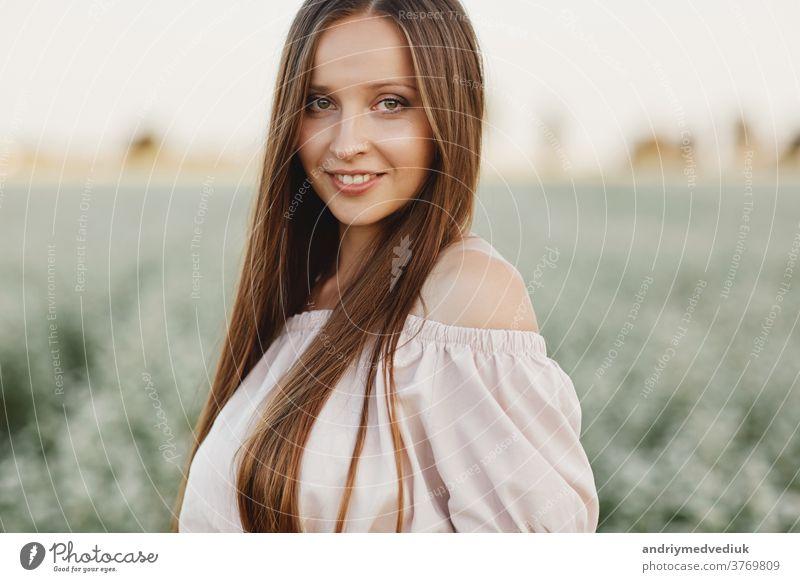 Schöne Frau genießt Feld, glückliche junge Dame und frühlingsgrüne Natur, Harmoniekonzept. Portrait eines schönen Mädchens in einem Blumenfeld. selektiver Fokus