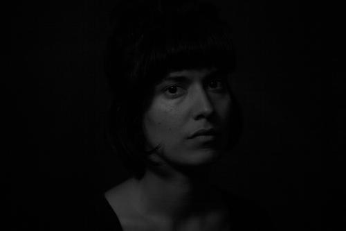 Schwarz-Weiß-Porträt eines indischen Mädchens auf schwarzem Hintergrund dramatisch Spannung Indiana schön sinnlich dunkel Traurigkeit beleuchtet obskur