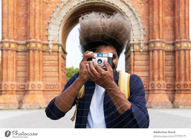 Schwarzer Mann, der ein Foto macht, während er mit der Kamera in die Kamera schaut Journalist Linse Bild Brühe modisch trendy Hobby Fotografie stylisch
