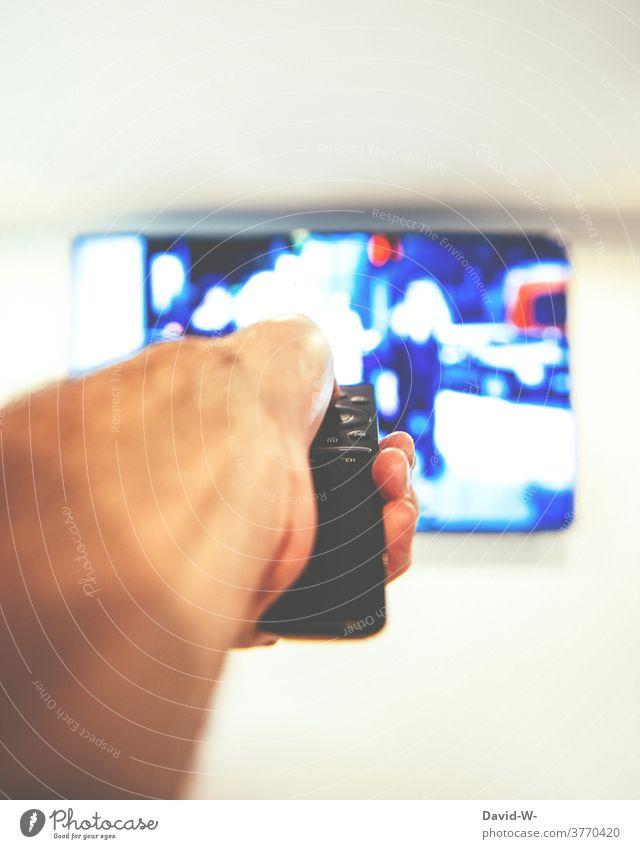 fernsehen und das Programm einstellen TV Fernbedienung Fernsehen Fernseher Hand bedienen Technik Mann anstellen Bildschirm Medien FERNSEHER