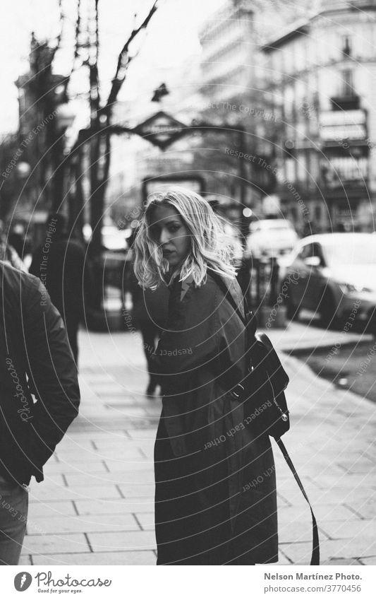 Porträt einer kaukasischen Blondine, die auf der Straße geht. Ubanischer Hintergrund. urban blond Russisch Frau Lifestyle Schwarzweißfoto Mensch Kaukasier
