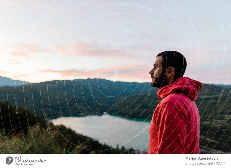 Junger Mann genießt den Blick auf den See bei Sonnenuntergang Abenteuer abenteuerlustig allein lässig Kontemplation Morgendämmerung Ausflugsziel Abenddämmerung