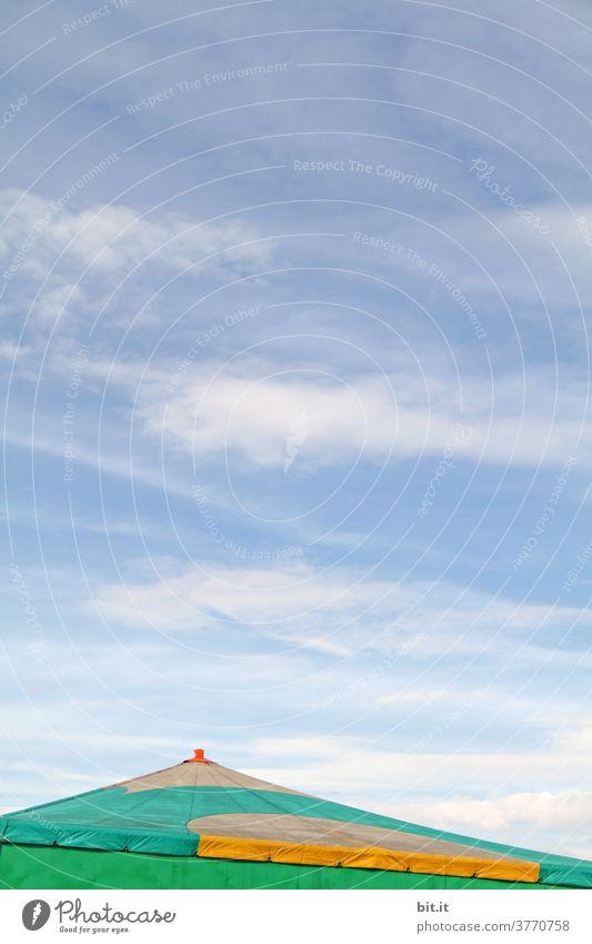 Schräges Dach vom Zirkuszelt, vor blauem Himmel. Zelt Zeltplane Zeltdach oben Anschnitt copyspace copy space Textfreiraum Wolken Horizont schräg bunt farbig