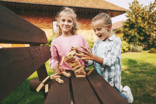 Zwei Mädchen haben Spaß und spielen draußen in der Nähe ihres Hauses ein Holzbrettspiel. Spiel heimwärts Kinder Freizeit Entwicklung Baum Schwester drei Glück