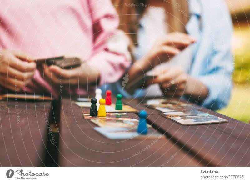 Zwei Schwestern lachen und spielen draußen vor ihrem Haus ein Holzbrettspiel mit bunten blauen, roten, grünen und gelben Chips. Spiel Kinder Freizeit